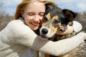 a smiling woman hugs her dog