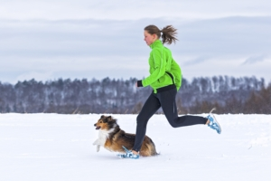 woman running with dog in winter